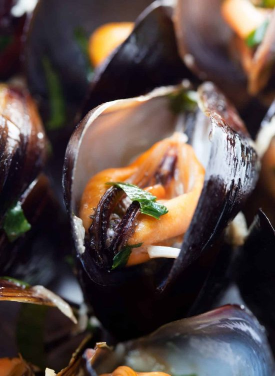 Black mussels on plate with green